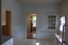 View into back hallway from kitchen including built-in cabinet