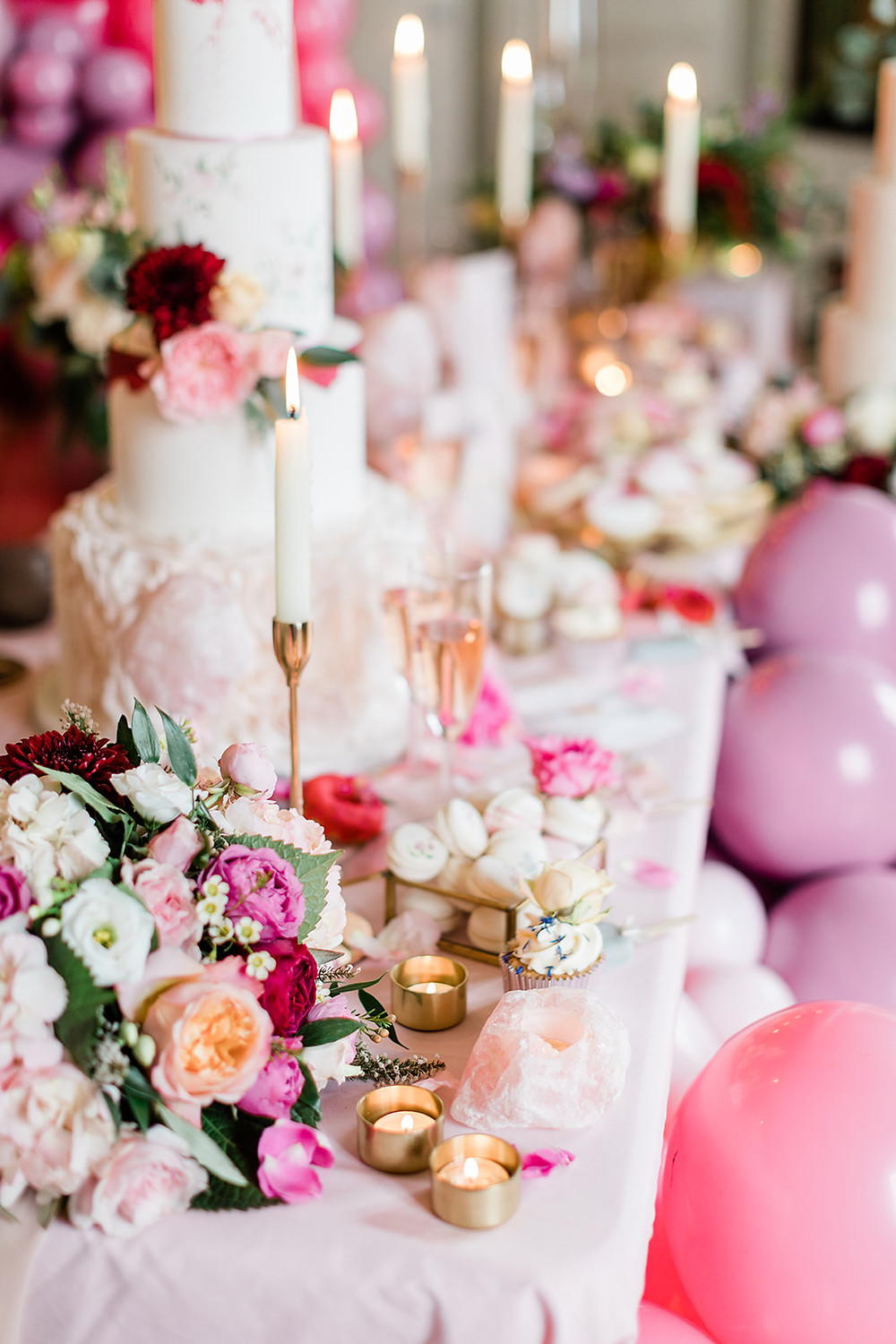 Table Beautifully decorated for a wedding meal with flowers, centrepieces, props in gold and pink. Capheaton Hall Northumberland wedding cake balloons