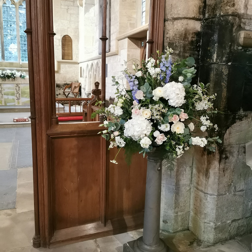 Covid19 safe church micro wedding at St Wilfreds Church in kirkharle Northumberland. Pedestal arrangement with scented white flowers David Austin Roses, light pink spray roses and blue delphinium. Floral Quarter Wedding Florist