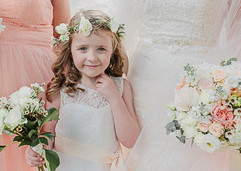 Flowergirl wearing a flower crown and carrying a small posy of flowers at a Newton Hall Wedding