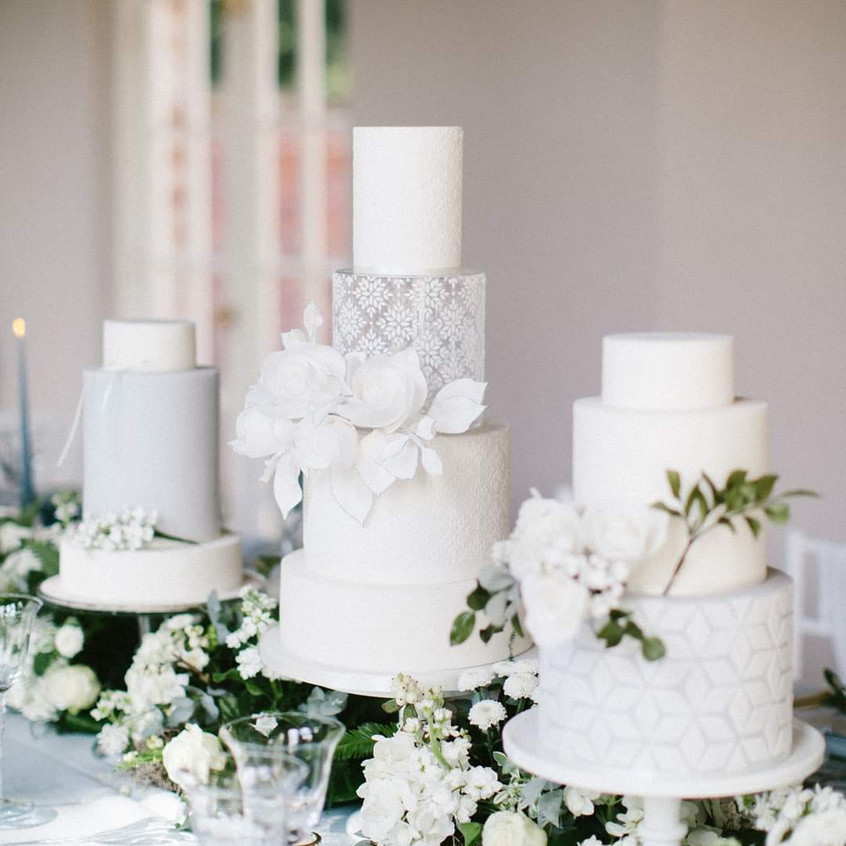 Wedding cake in white and grey blue colour scheme, on a long banqueting table for a micro wedding at Newby Hall Orangery in Yorkshire. Luxe white wedding flowers and greenery foliage. Wedding florist yorkshire