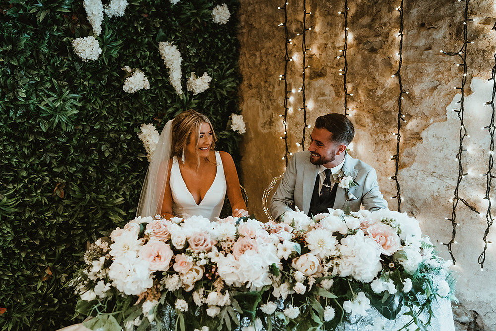Charlton hall wedding ceremony. Bride and groom getting married signing the register behind white and blush flowers