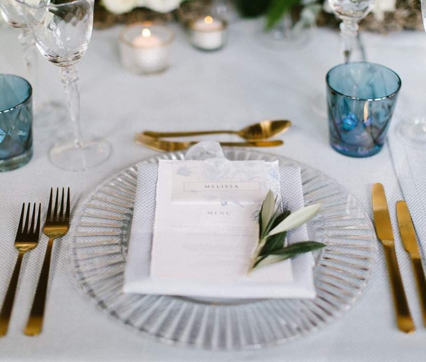 Micro wedding dining table in dusty blue and grey with gold cutlery. Olive leaf accent on the place setting. Wedding photoshoot at Newby Hall Orangery in Yorkshire
