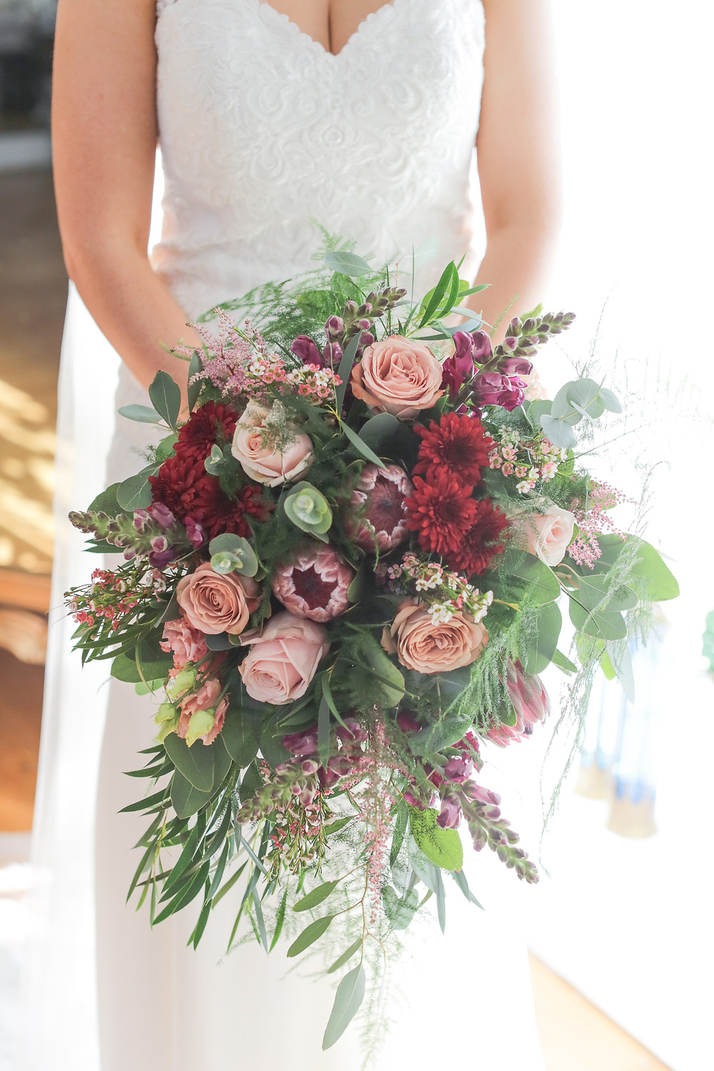 Cascading Autumnal Hand Tied bridal bouquet wedding flowers at Woodhill Hall Northumberland with red blush pink and foliage. Image by Helen Russell Photography