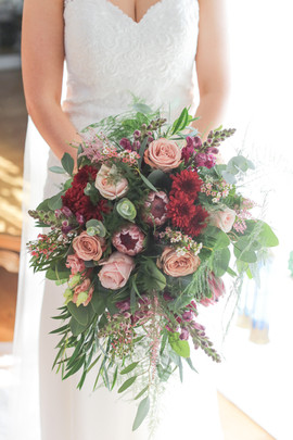 Trailing dark red autumnal bridal bouquet at Woodhill Hall