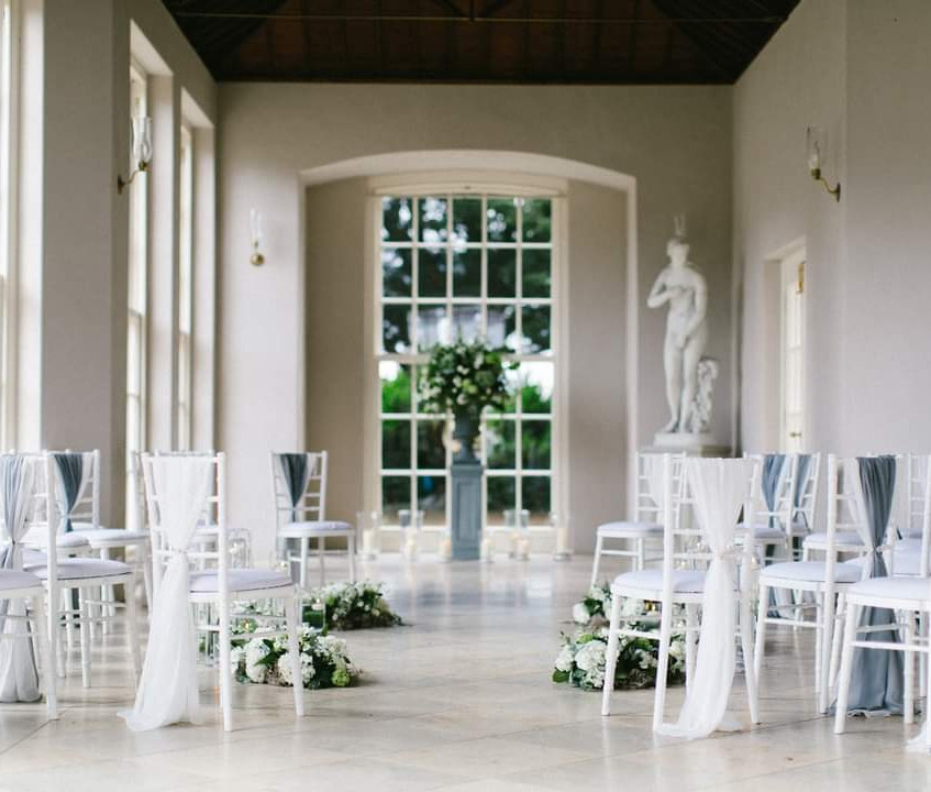 Micro Wedding ceremony circular seating set up at Newby Hall Orangery in Yorkshire. Grey and dusty blue colour scheme with white wedding flowers Yorkshire and candles with greenery