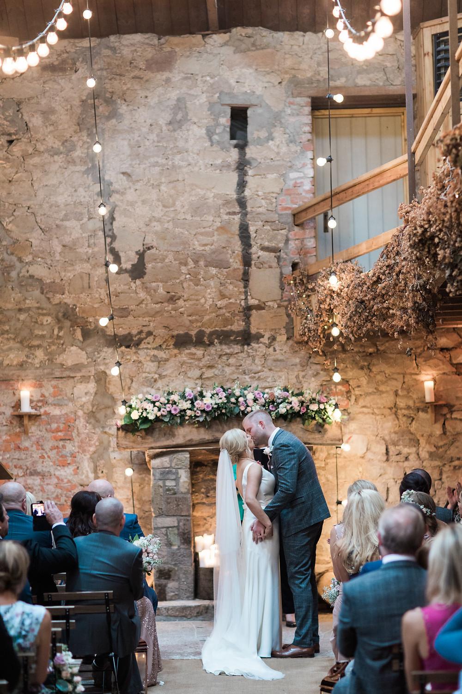 DOxford barns wedding ceremony threshing hall with wedding flowers on fireplace