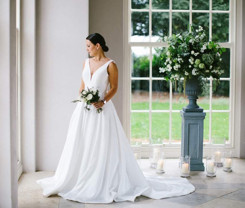 Large urn flower arrangement at Newby Hall Orangery in Yorkshire. Bride in her wedding dress holding her wedding Flower bouquet with white roses and olive leaf.