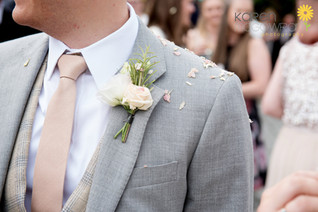 Pale pink Rose buttonhole and grey suit