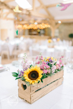 Rustic colourful summer flower centrepieces at Doxford BArns in Northumberland