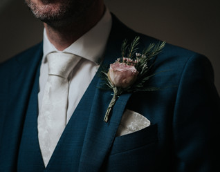 Pink Rose buttonhole on navy suit