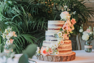 Semi Naked wedding cake with garland of fresh flowers at NEwton Hall