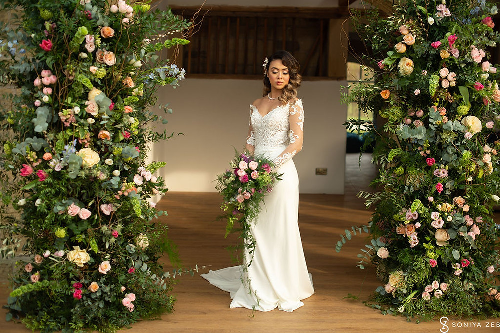 Harewood house the hovels large floral columns stand either side of the Bride with her bouquet at this beautiful yorkshire wedding photo shoot
