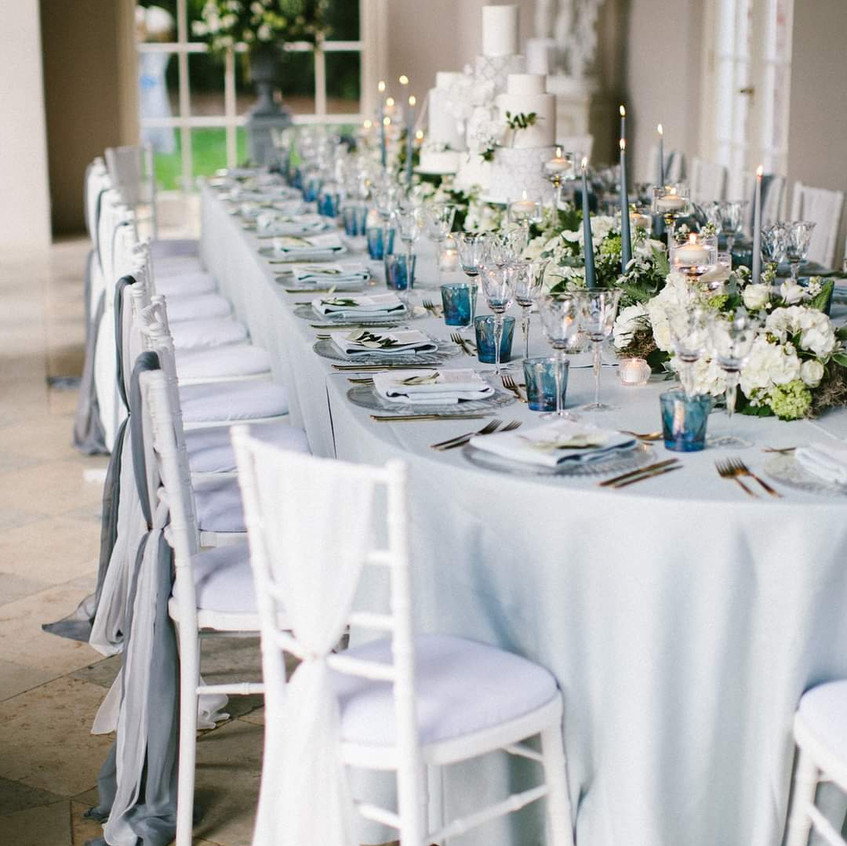 Luxe Micro wedding in Blue and Grey colour scheme at Newby Hall Orangery in Yorkshire. White flowers and foliage along the full length of the table and pale blue and grey tones with candles and crockery. Hanging floral display from the ceiling too.