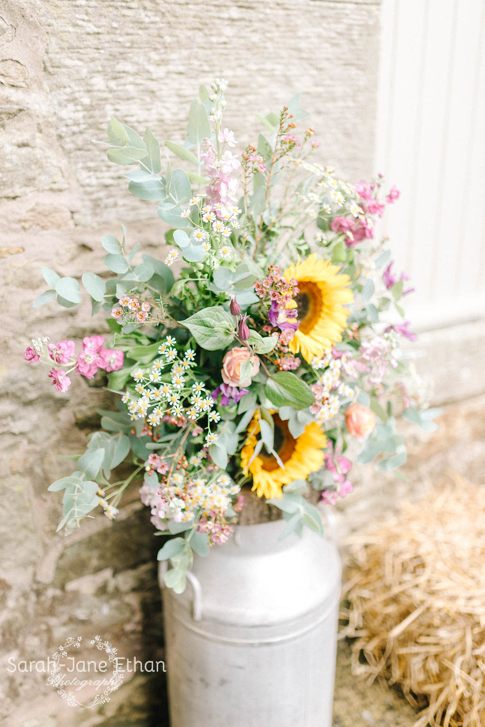 Milk churns with colourful summer wedding flowers waiting outside of the Threshing Hall wedding ceremony room at Doxford Barns in NOrthumberland
