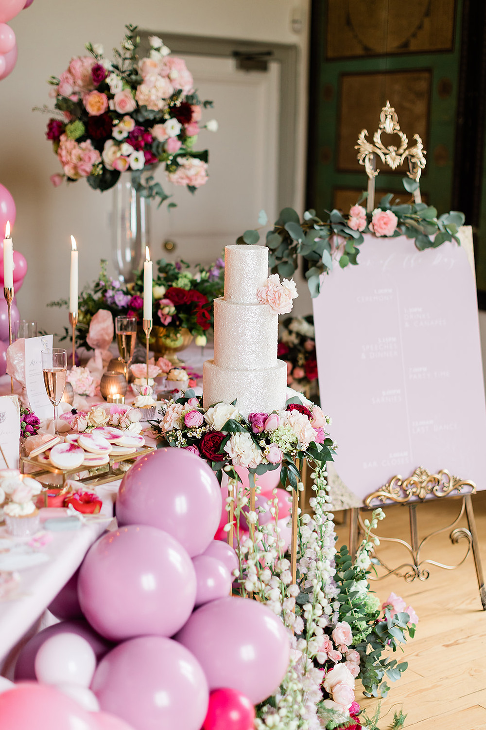 Table Beautifully decorated for a wedding meal with flowers, centrepieces, props in gold and pink. Capheaton Hall Northumberland wedding ckae flowers florist balloons