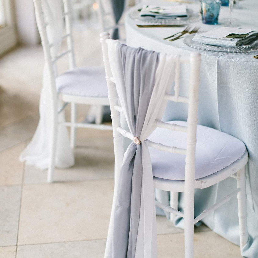 Luxe Micro wedding in Blue and Grey colour scheme at Newby Hall Orangery in Yorkshire. White flowers and foliage along the full length of the table and pale blue and grey tones with candles and crockery. White and grey chiffon chair drops