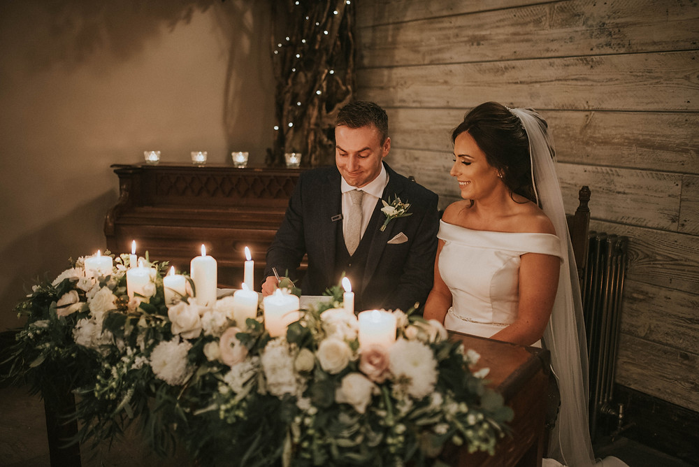 South Causey Inn - The Old Barn Wedding Ceremony. Bride and Groom sitting at the registrar table signing the register behind their wedding flowers and candle light
