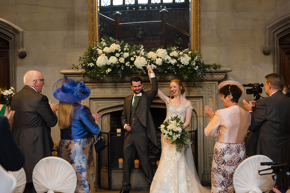 MAtfen HAll wedding ceremony fireplace flowers Bride and groom celebrating getting married!