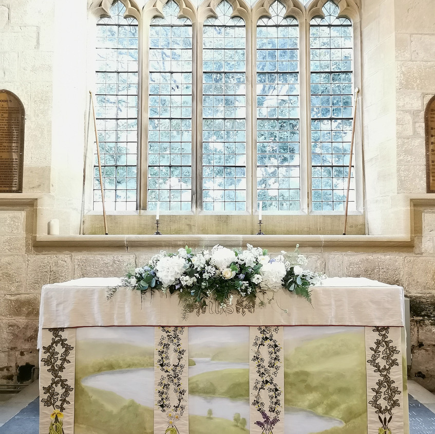 Covid19 safe church micro wedding at St Wilfreds Church in kirkharle Northumberland. Altar flower arrangement with scented white flowers David Austin Roses, light pink spray roses and blue delphinium. Floral Quarter Wedding Florist