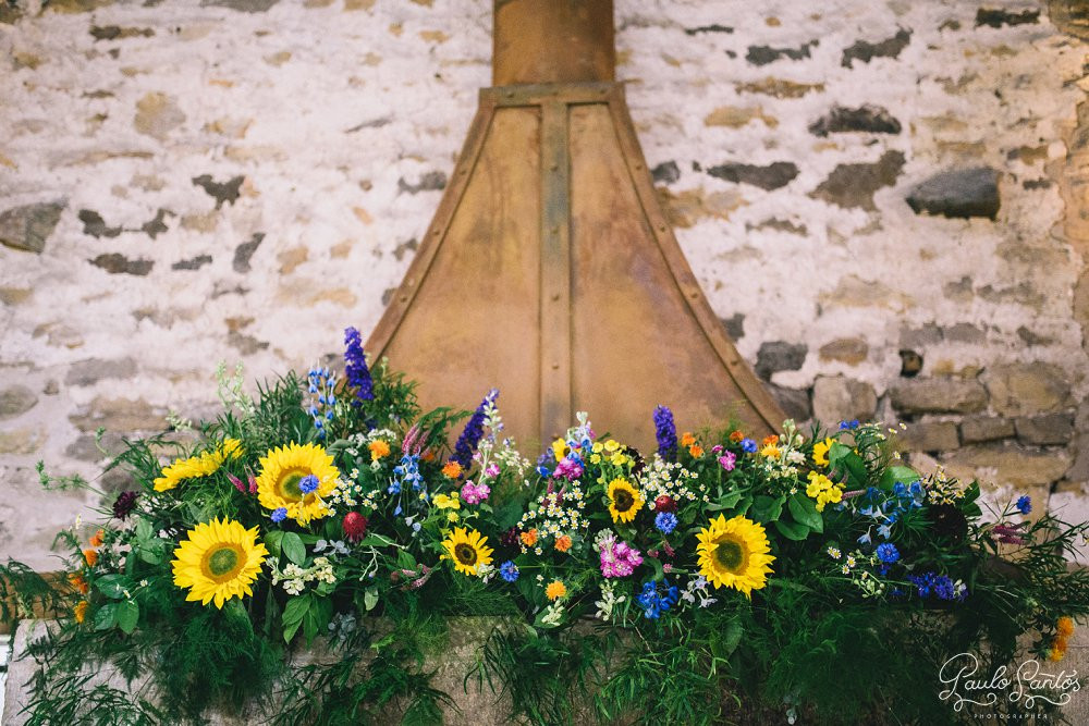 colourful barn wedding summer flowers on fireplace at healey barn wedding ceremony in northumberland.