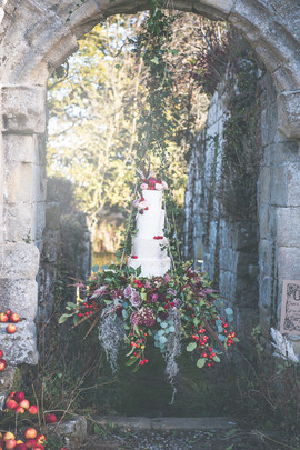 Hanging Wedding Cake display with fresh flowers and foliage trailing down at Jervaulx Abbey Yorkshire