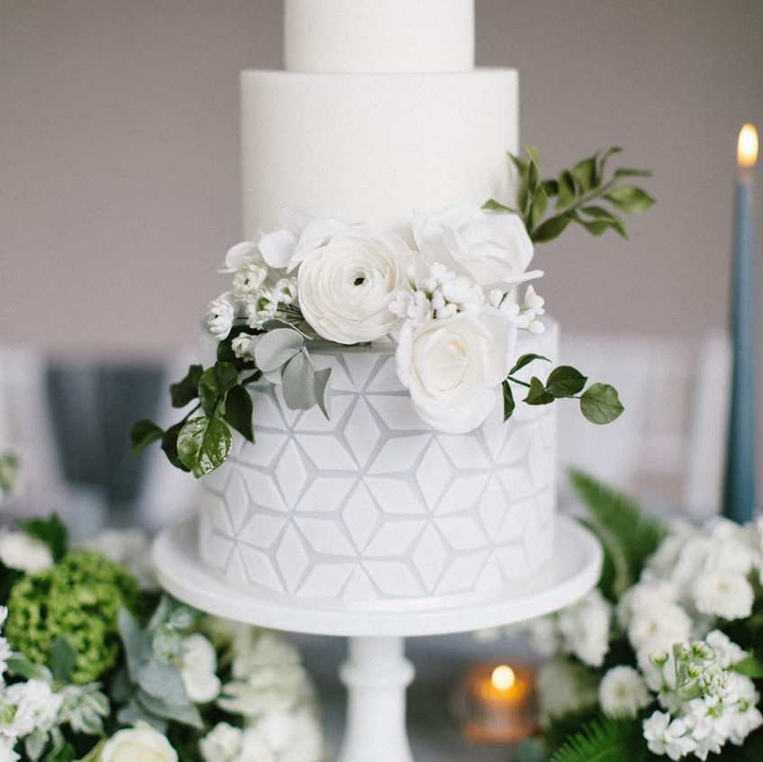 Wedding cake by Poppy Pickering with fresh white wedding flowers and greenery. At Newby Hall Orangery in Yorkshire
