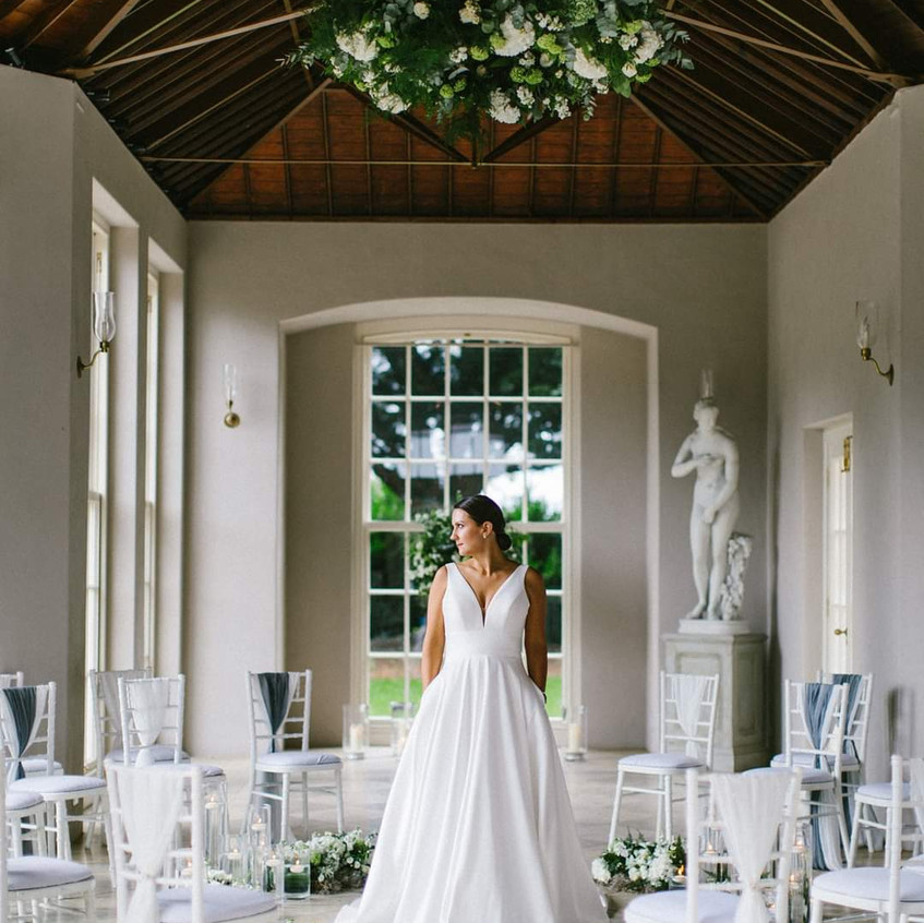 Micro Wedding ceremony circular seating set up at Newby Hall Orangery in Yorkshire. Grey and dusty blue colour scheme with white wedding flowers Yorkshire and candles with greenery. Bride in her wedding dress standing in the middle