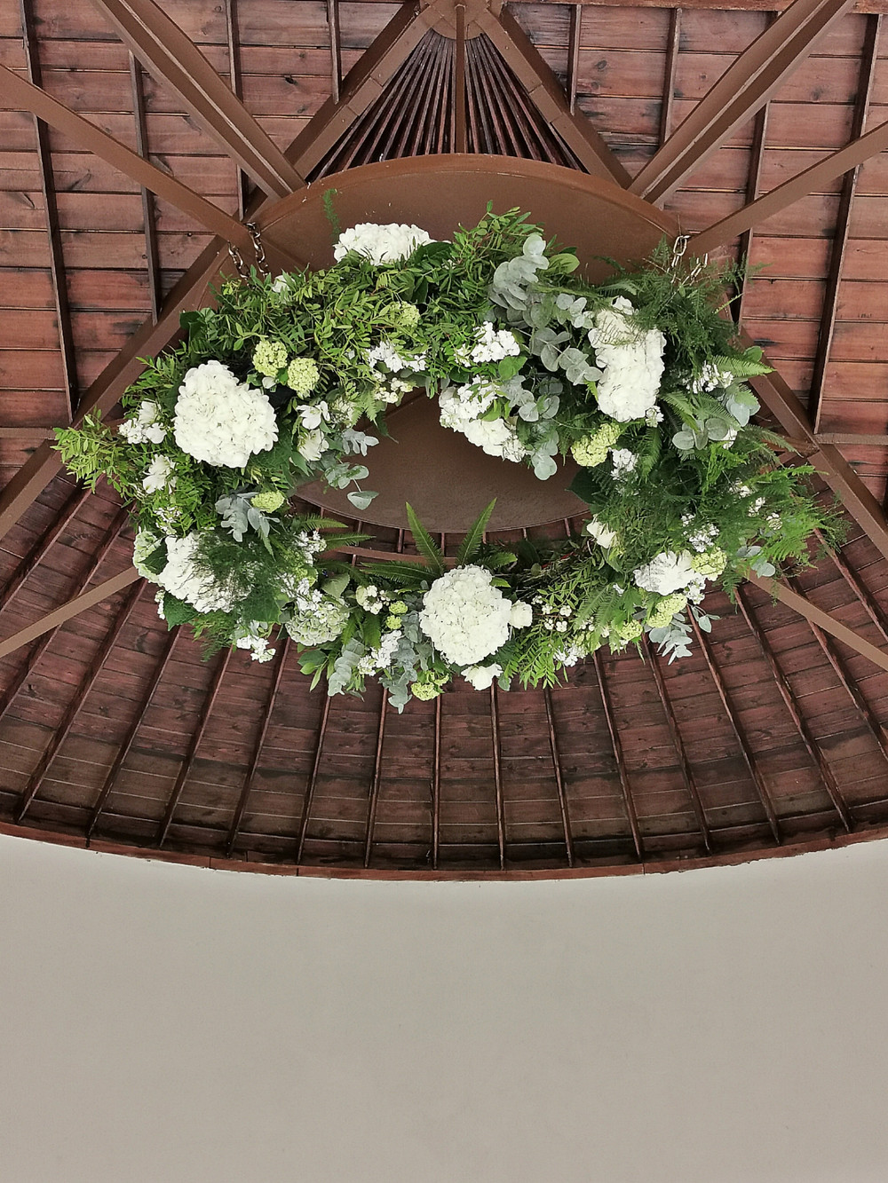 Stunning large hanging floral display in the ceiling of Newby Hall Orangery in Yorkshire, with classic white and green wedding flowers
