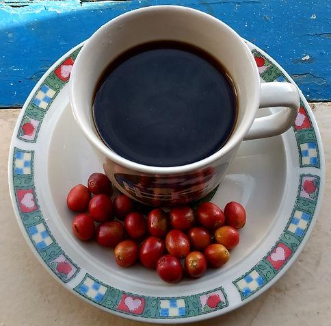 Xícara de café coado com grãos de café cereja
