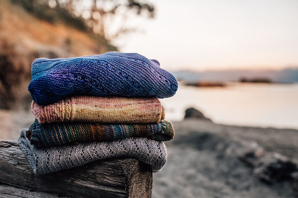 A stacked pile of knit items, sweaters ans shawls, placed on a log at a sunset filled beach.