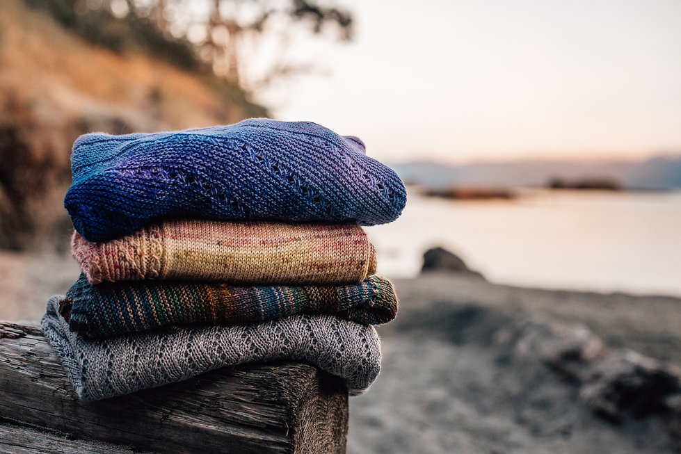 Stack of knitting on a beach at sunset