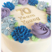 Floral buttercream cake with gold fondant lettering