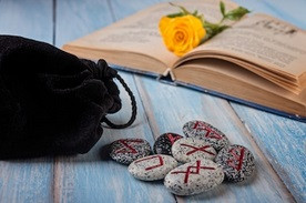 Bag of Runes With a Rose on an Open Book.