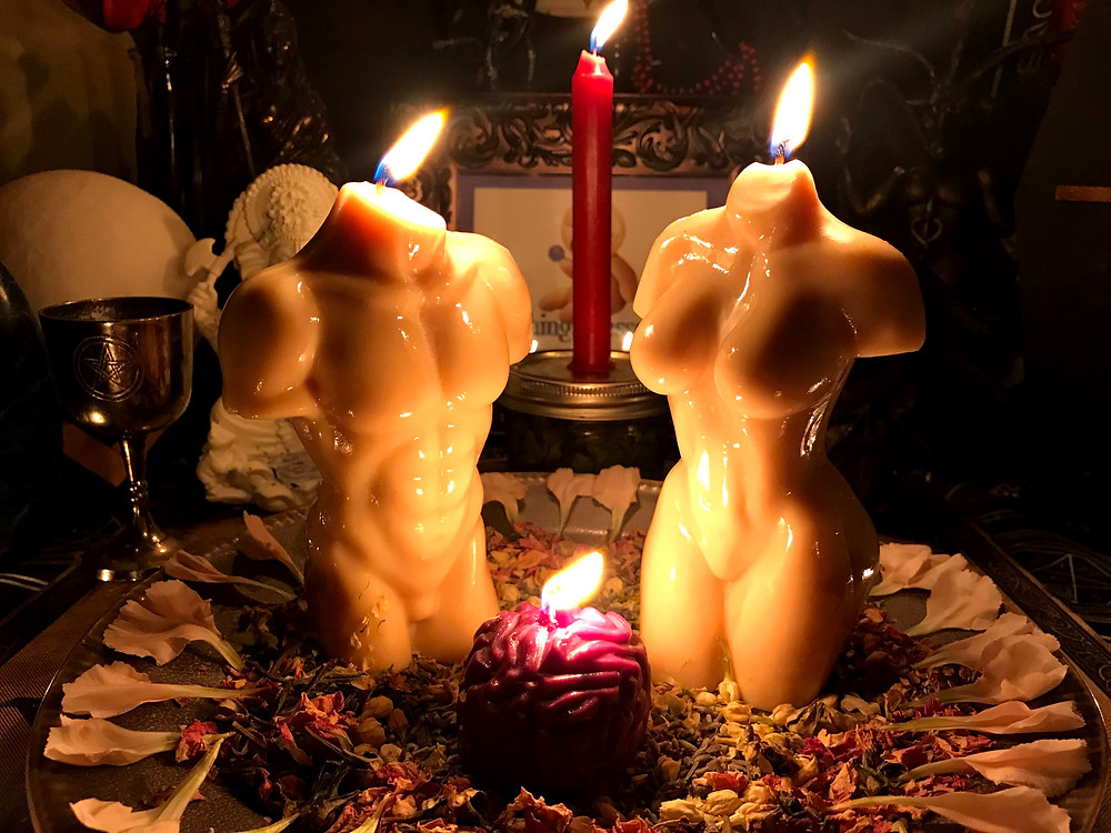 Male and female white torso candles with a purple brain candle in the center.