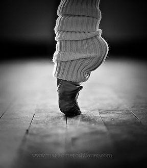 voet in balletschoen met enkelwarmer