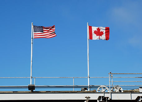 Flags flying at a US and Canadian border