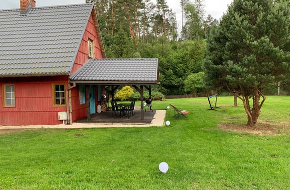 Domek - w drugim planie widok na las, który bezpośrednio sąsiaduje z działką