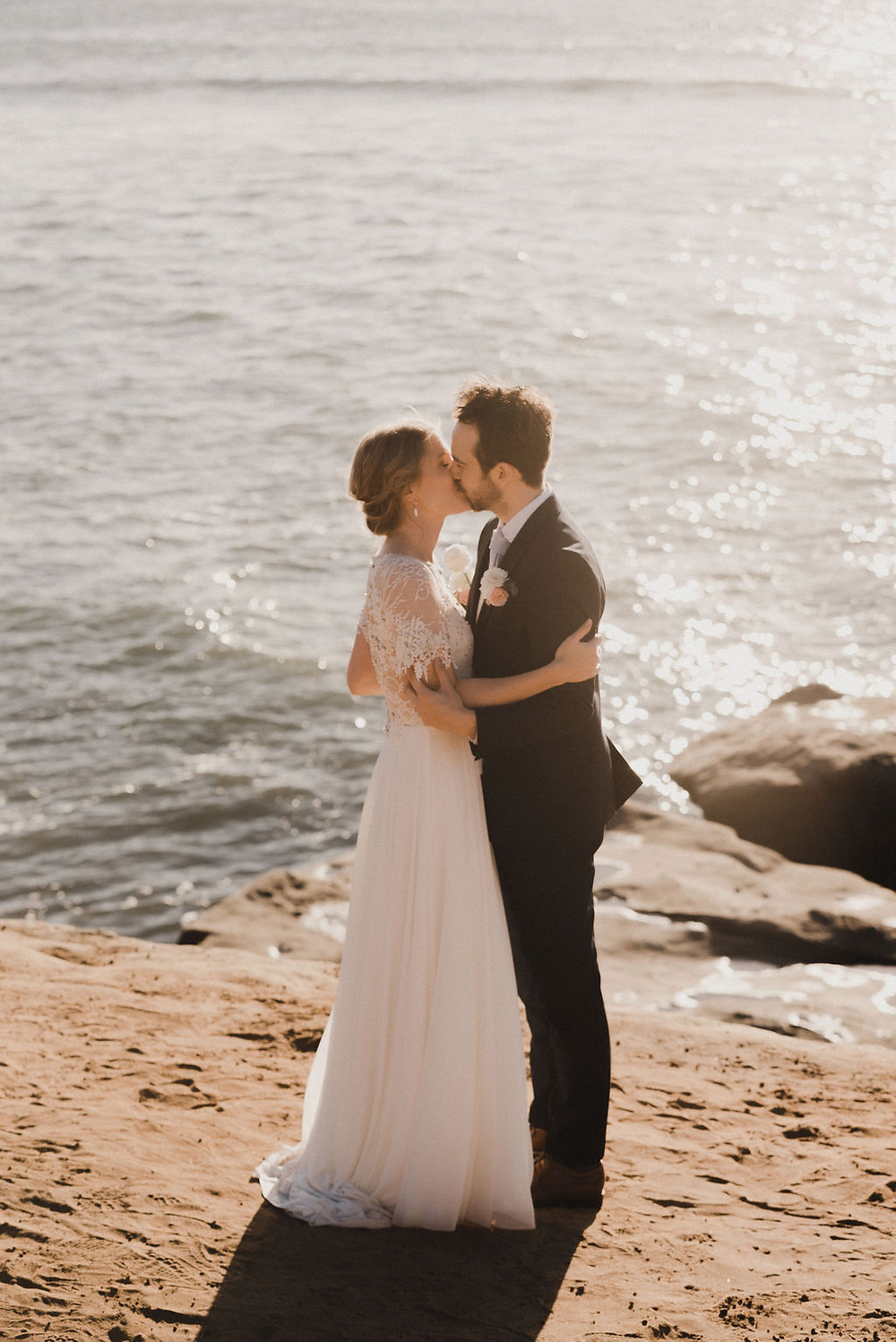 Bride and groom kissing at Sunset Cliffs