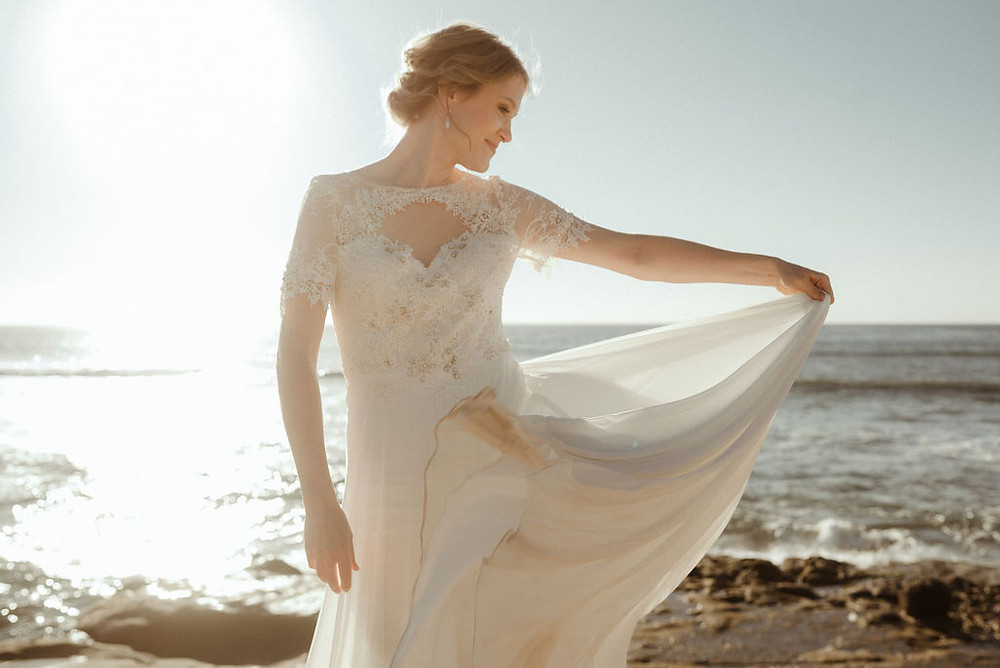 Bride holding dress by the ocean