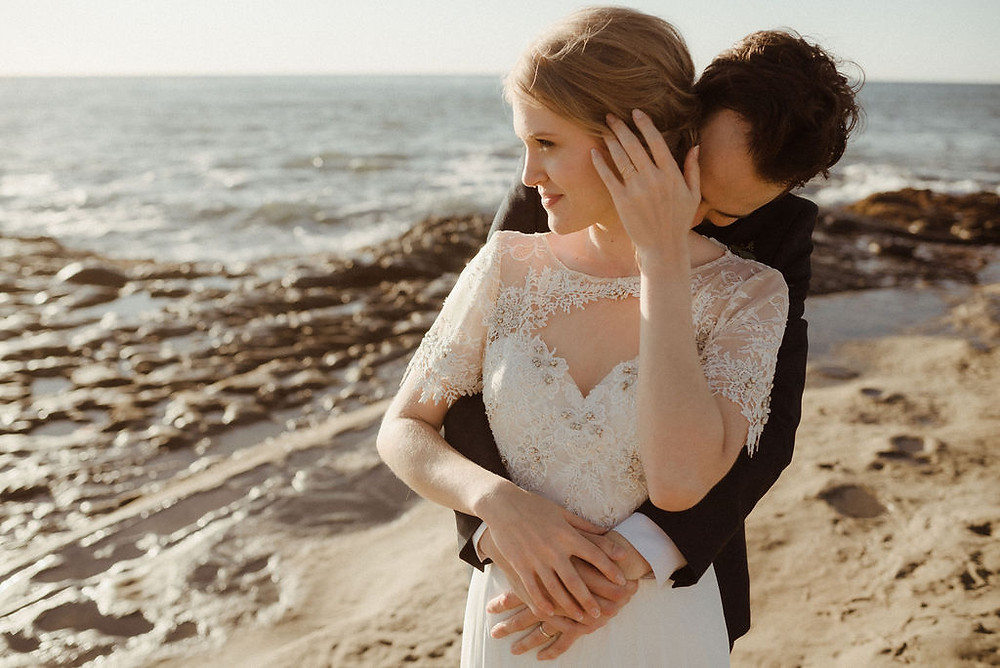 Bride and groom posing at Sunset Cliffs
