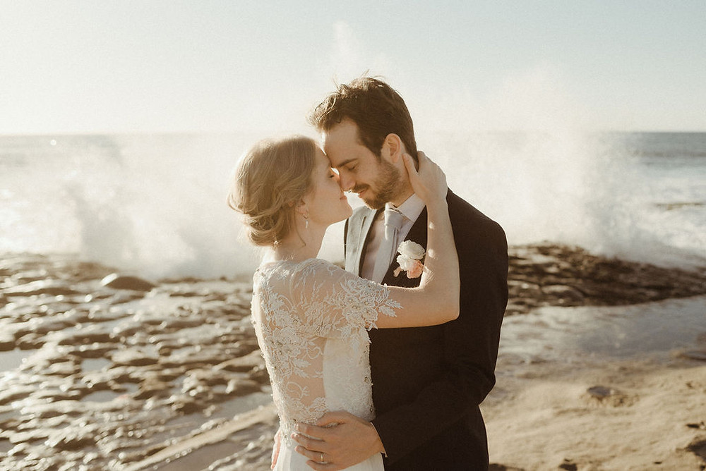 Bride and groom with waves crashing behind them