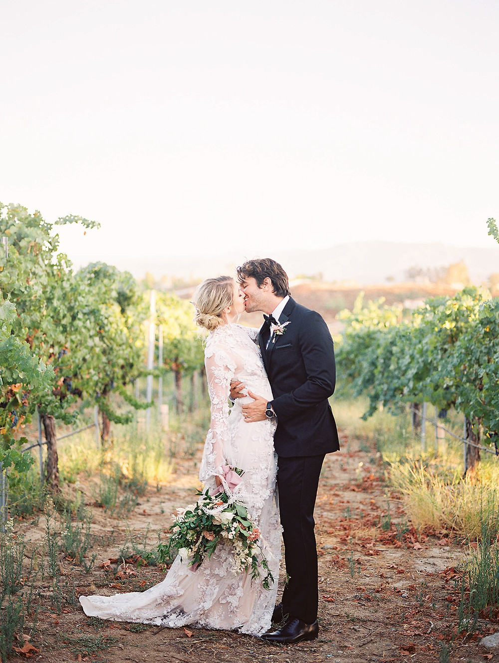 bride and groom kissing in grapevine field at Avensole Winery Wedding