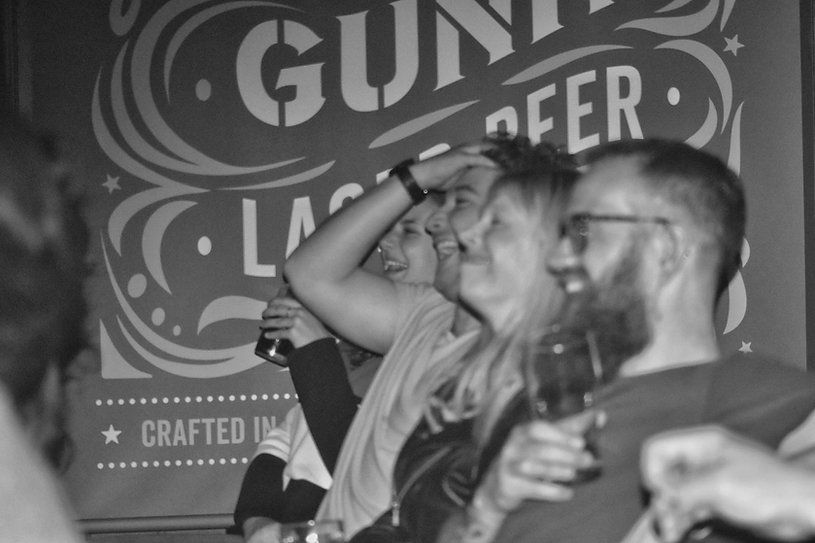 People laughing at a comedy night, and drinking beer.