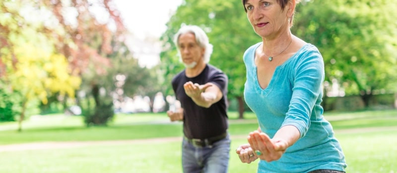 couple doing tai chi in park