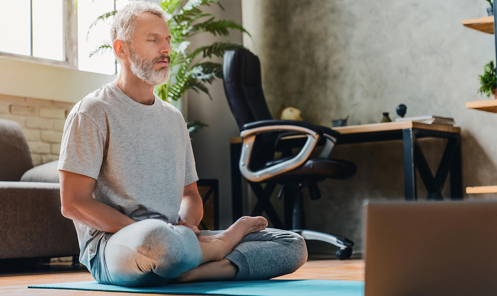 older man doing yoga at home with laptop
