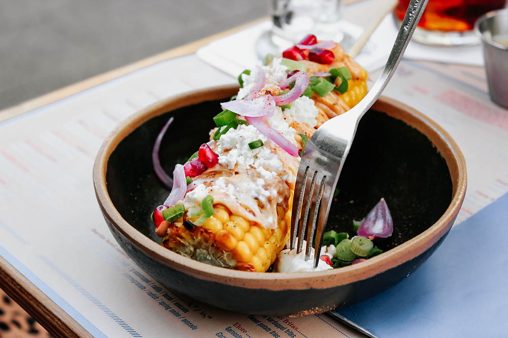 Corn in bowl with vegetables, sour cream and a fork