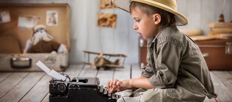 young boy using typewriter