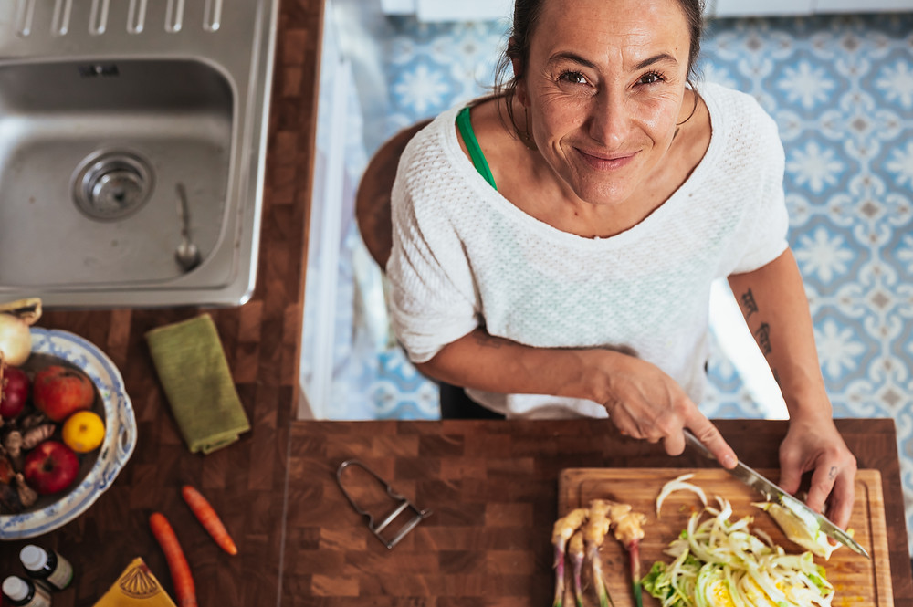 Older woman chopping vegetables in kitchen