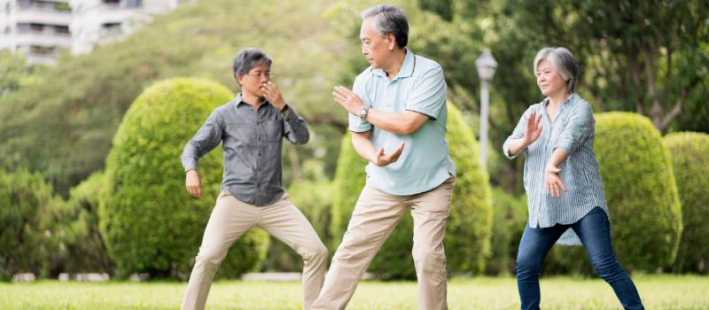 3 seniors doing tai chi outside